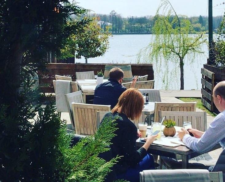 oameni luand masa la terasa de langa lac Herastrau Il Locale