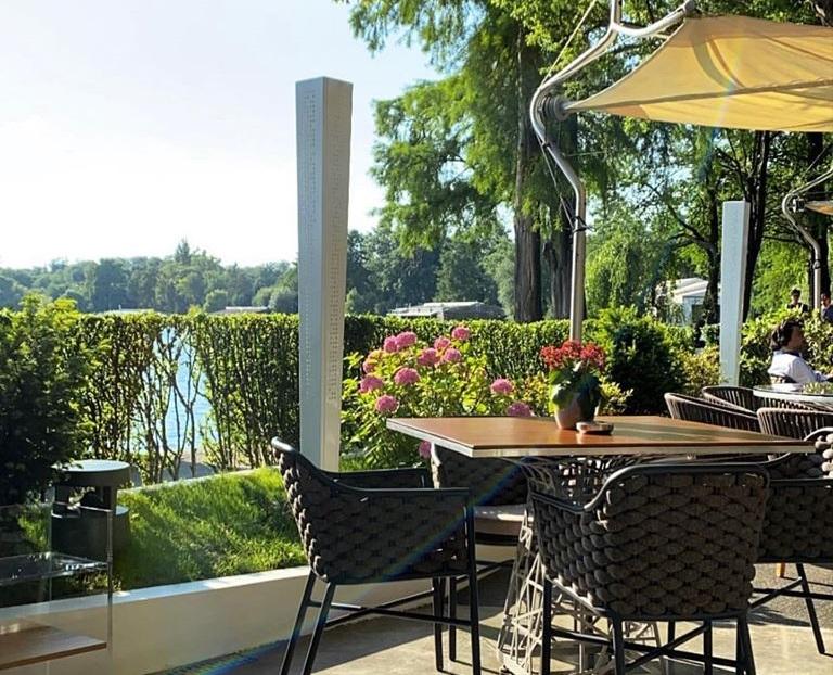 prim plan cu o masa cu scaune de rachita si umbrela, terasa langa lac, la Casa di David, in Herastrau