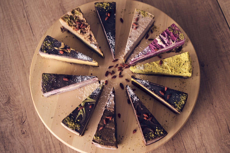 felii de tortu raw vegan, diferite sortimente asezate in cerc pe un platou de lemn
