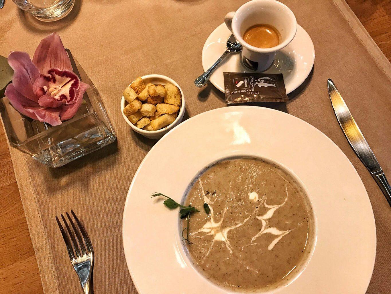 supa crema de ciuperci hribi cu crutoane in farfurie alba de supa, cu tacamuri in lateral, o ceasca de cafea langa