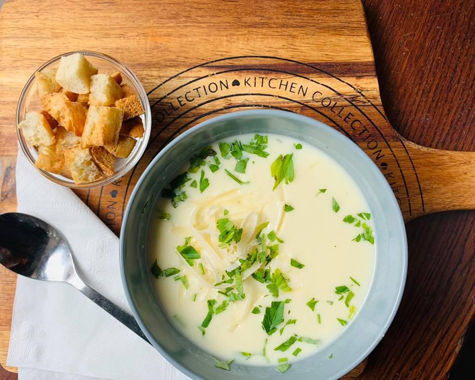 bol de supa albastru, pe masa maro, cu supa crema de usturoi si verdeata, crutoane asezate langa
