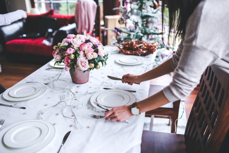 femeie aranjand masa la restaurant pentru organizarea Revelionului, cu farfurii, tacamuri si ghiveci cu trandafiri roz