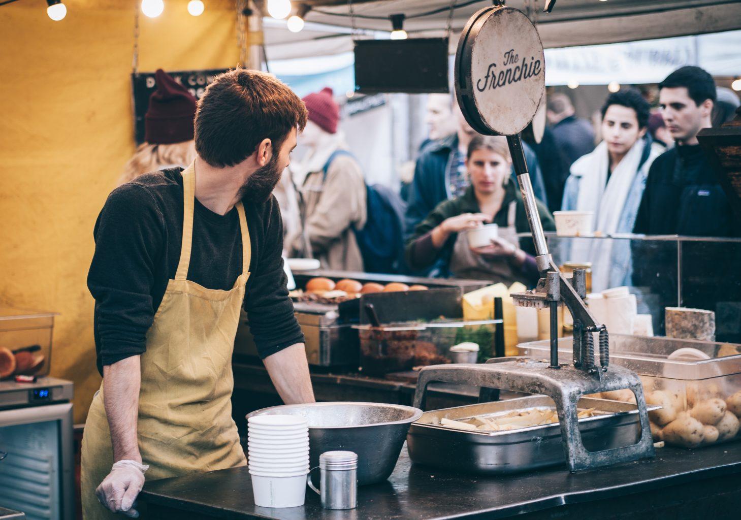 barman in spatele tejghelei privind catre restaurantul plin de oameni, imagine reprezentativa pentru burnout-ul angajatilor din restaurante