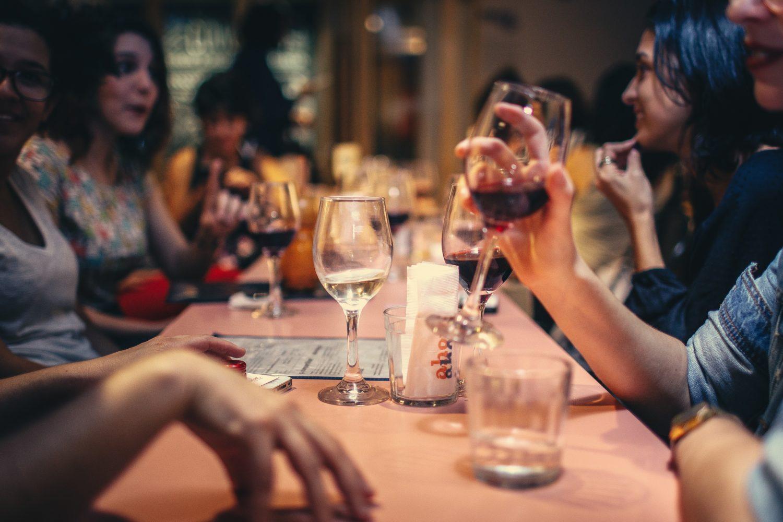 close upcu un grup de prietenistand impreuna la masa, de vorba, si band alcooln