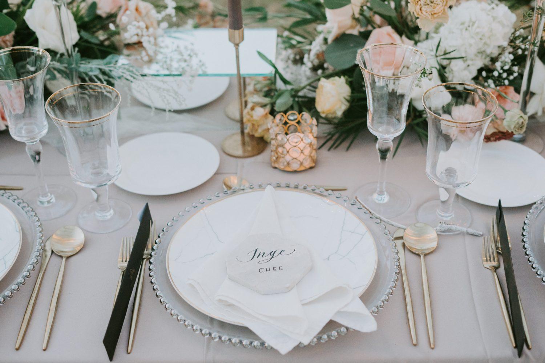 close up reprezentativ pentru codul bunelor maniere la masă, cu un aranjament elegant, cu farfurii albe si tacamuri elegante, pahare de cristal si aranjamente florale pe masa