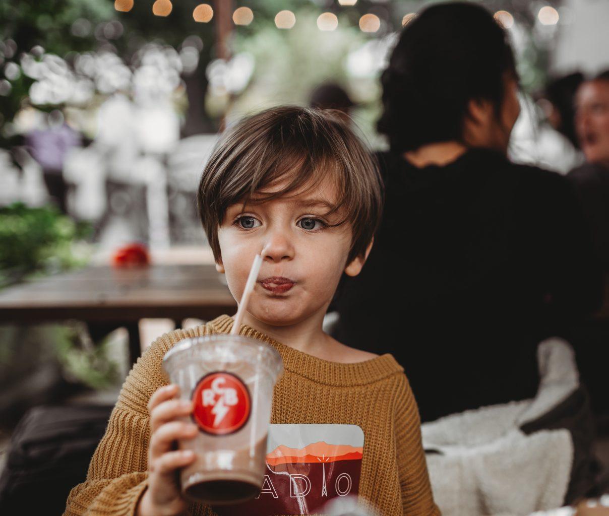 baietel sorbind suc cu paiul dintr-un pahar transparent e plastic