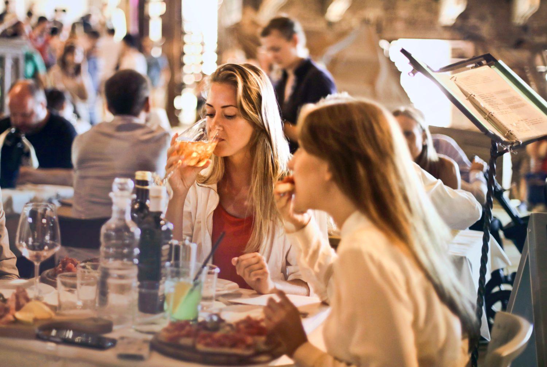 două femei luând masa la restaurant, una dintre ele sorbind vin din bahar