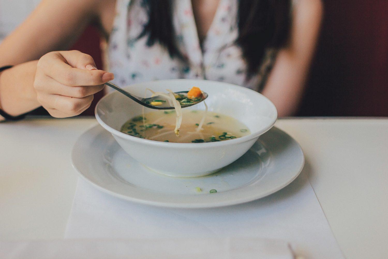 close up cu o femeie careia nu i se vede fata si care ia cu lingura supa de taitei dintr-un bol alb
