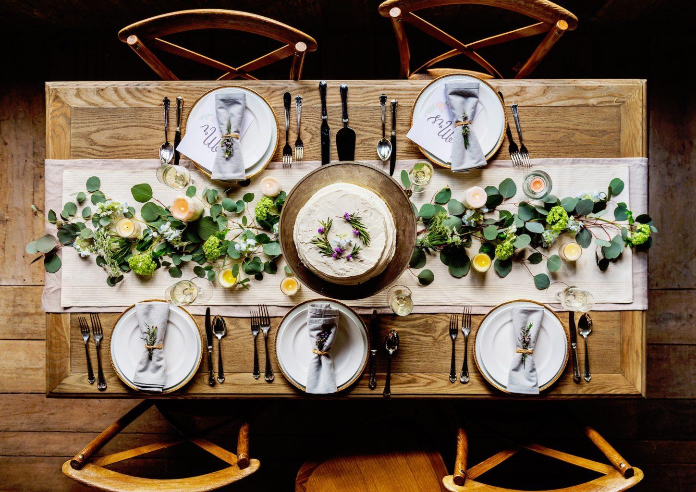 imagine fotografiata de sus a unei mese de lemn aranjata festiv, cu cinci seturi de farfurii si tacamuri si flori decorative in centrul mesei