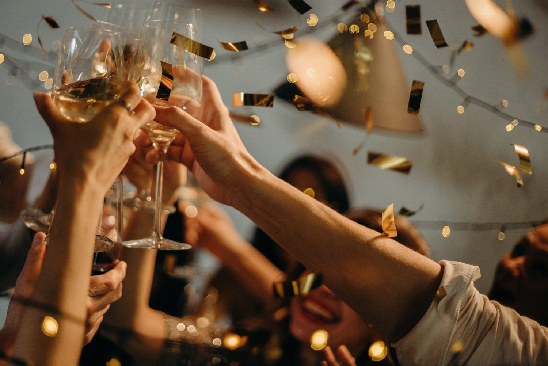 Oameni la petrecere de Revelion ciocnind pahare de vin