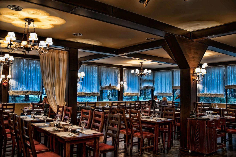 Imagine de ansamblu din restaurantul Il Calcio by mr. Val, cu multe mese de lemn si ferestre mari in fundal, un loc perfect pentru o cină festivă