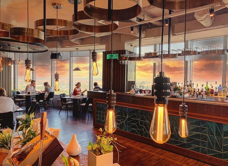 vedere de ansamblu din restaurantul Nor, cu mese asezate langa ferestrele mari si corpuri de iluminat in prim plan