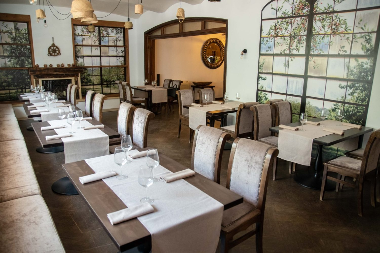 Imagine din interiorul restaurantului Rost, cu mese si scaune capitonate si decoratiuni pe pereti