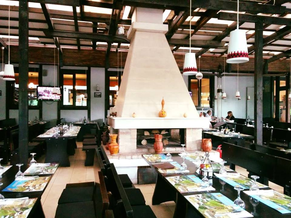 imagine din interiorul restaurantului Taverna Sarbului, cu mese de lemn in prim plan si semineu mare, alb, in plan secundar