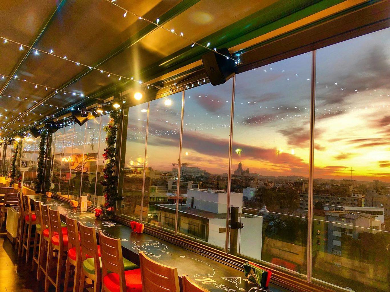 vedere spre geamurile mari ce ofera o priveliste minunata asupra Bucurestiului, de la Upstairs Rooftop, un restaurant perfect pentru o cină festivă