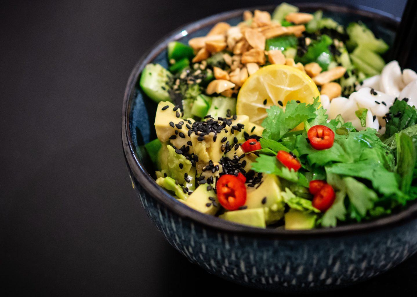 salata de post cu lamaie, salata verde, alune, ardei rosu, avocado si salata verde,  in bol negru pe fundal negru