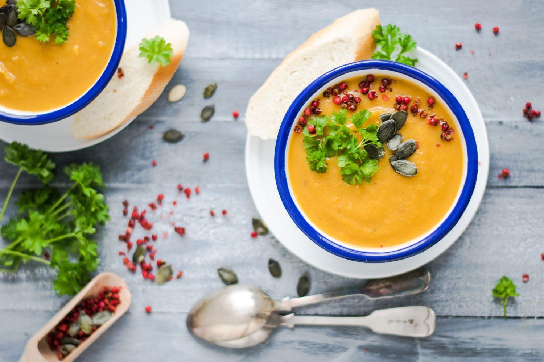 doua boluri cu supa crema de morcovi cu seminte, frunze de patrunjel si rodie raw vegan