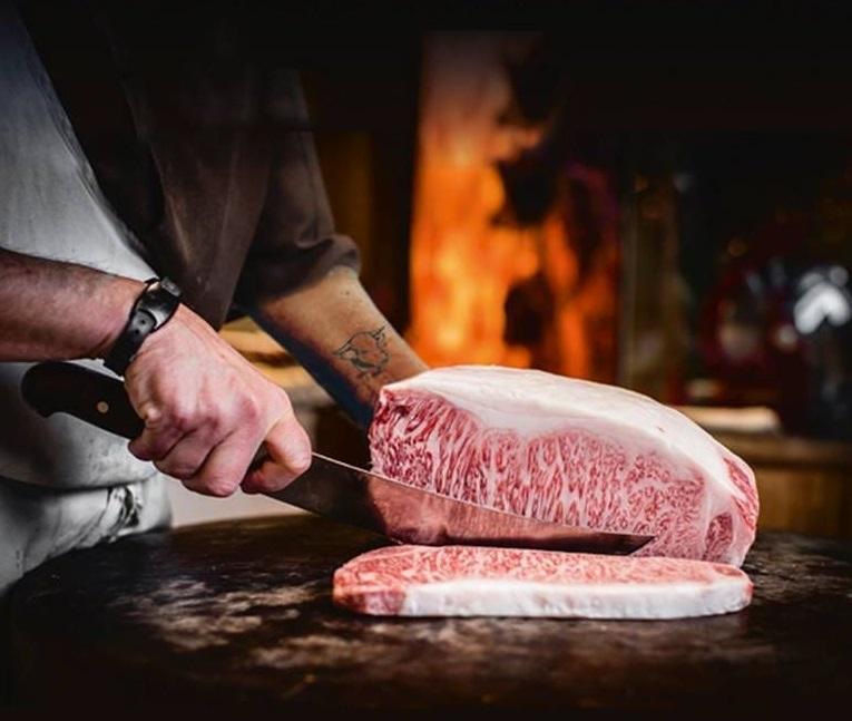 dry aged steak la VacaMuuu, bucata de carne de vita cruda, taiata cu cutitul de un bucatar, iar in fundal imagine cu un cuptor cu foc