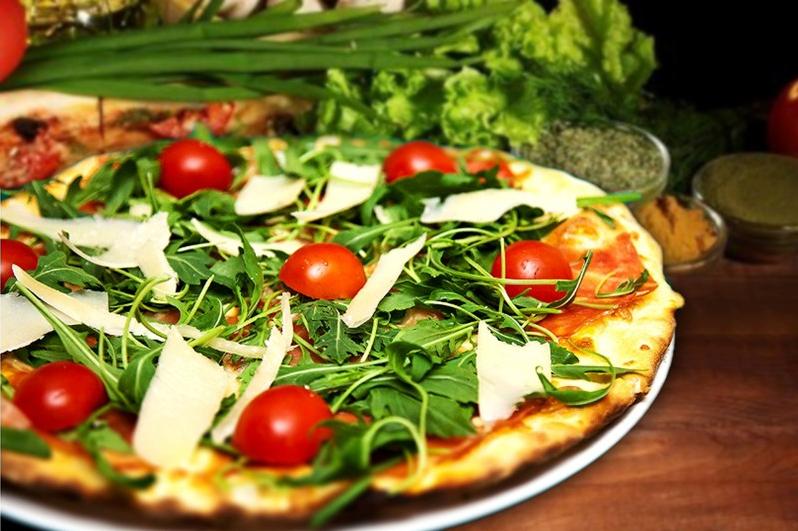 pizza romana cu rucola, parmezan si rosii cherii, cu verdeata in fundal, pizza italiană București