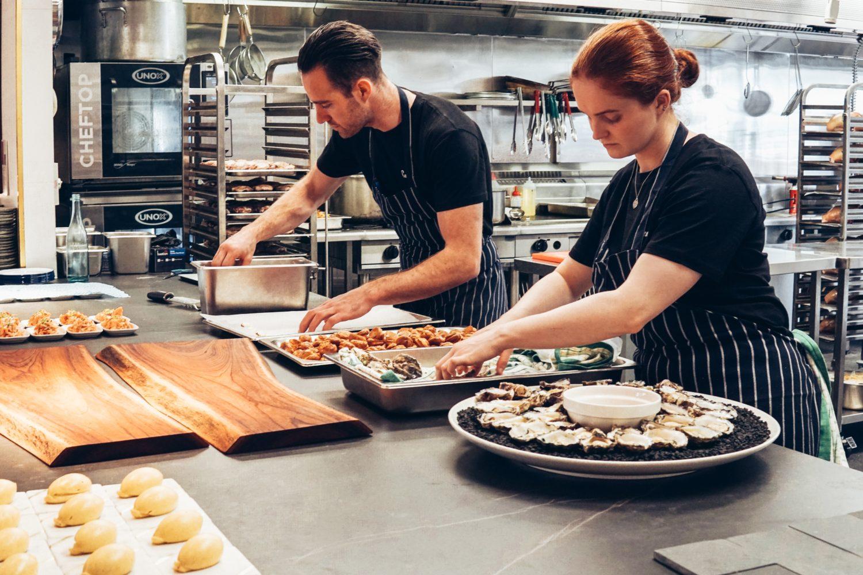 angajati in restaurant preparand mancare pe blat de lucru, in farfurii mari, rotunde - metode de a creste profitul unui restaurant