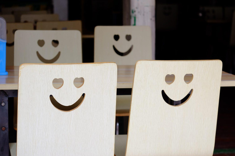 patru scaune de lemn, dintre care doua in prim plan, cu fete zambitoare decupate in lemn