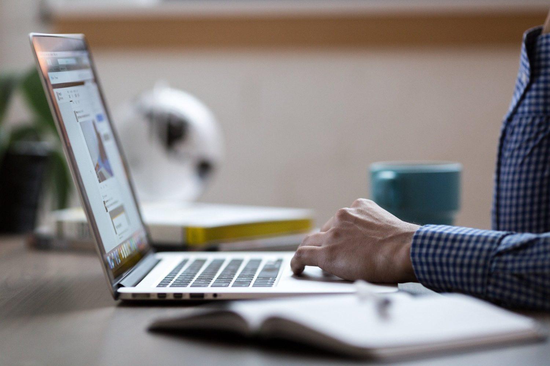 Barbat tastand la laptop, asezat la birou, cu o cana albastra langa, imagine sigestiva pentru un manager care reduce costurile directe in restaurant