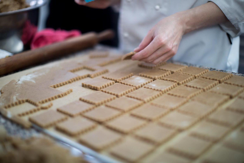 prim plan cu mana unui bucatar care prepara biscuiti din aluat fara gluten, intinsi pe masa si decupati patrat, de la Zexe Braserie