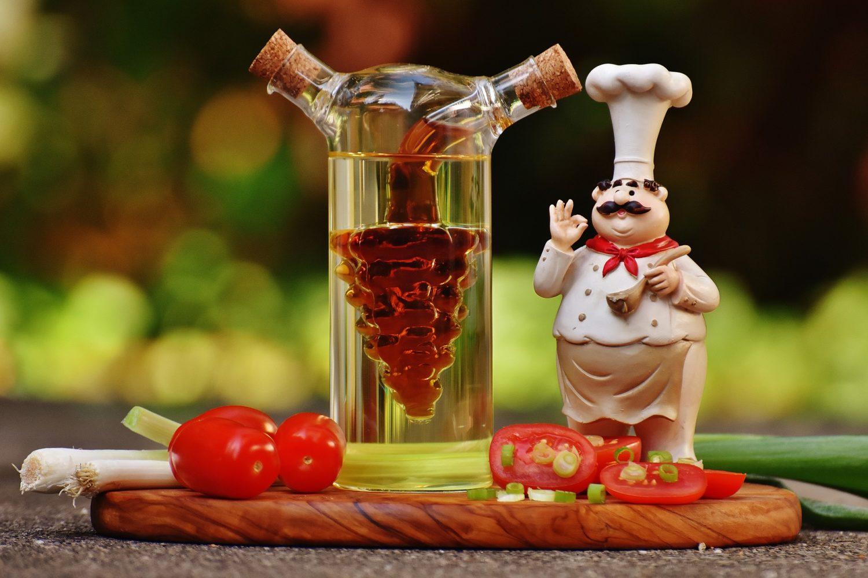 figurina bucatar, pe fund de lemn cu rosii si felii de rosii si o sticla de ulei si otet