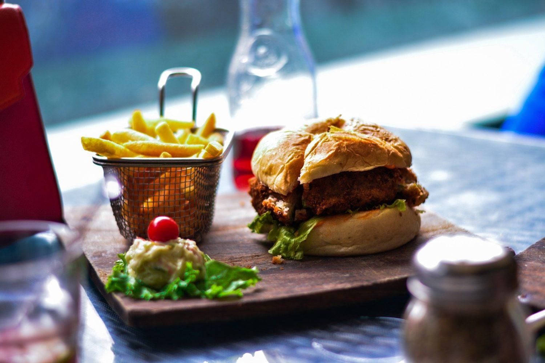 burger cu cartofi prajiti pe blat de lemn, cu verdeata si o rosie, burger fara carne, food trends