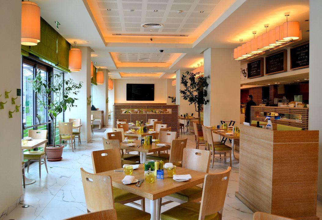 incapere luminoasa la caffe citta, cu ferestre mari, jaluzele verzi, mese si scaune din lemn si pereti albi