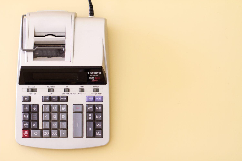 masina de calculat pentru birou, fotografiata de sus, pe fundal roz, imagine reprezentativă pentru cum se calculează costul primar