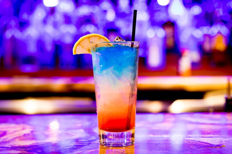 pahar de cocktail inalt, multicolor, cu albastru, alb si portocaliu, pe fundal albastru, unul din food trends pentru 2020