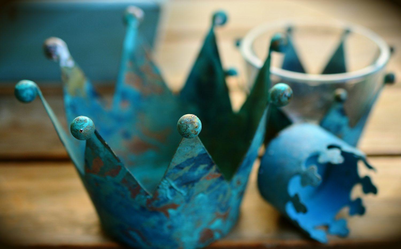 coroana metalica albastra, ruginita, in prim plan, asezata pe masa de lemn