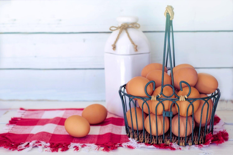 cos metalic cu mai multe oua asezat pe un stergar alb si rosu, cu alte doua oua langa si o sticla de lapte