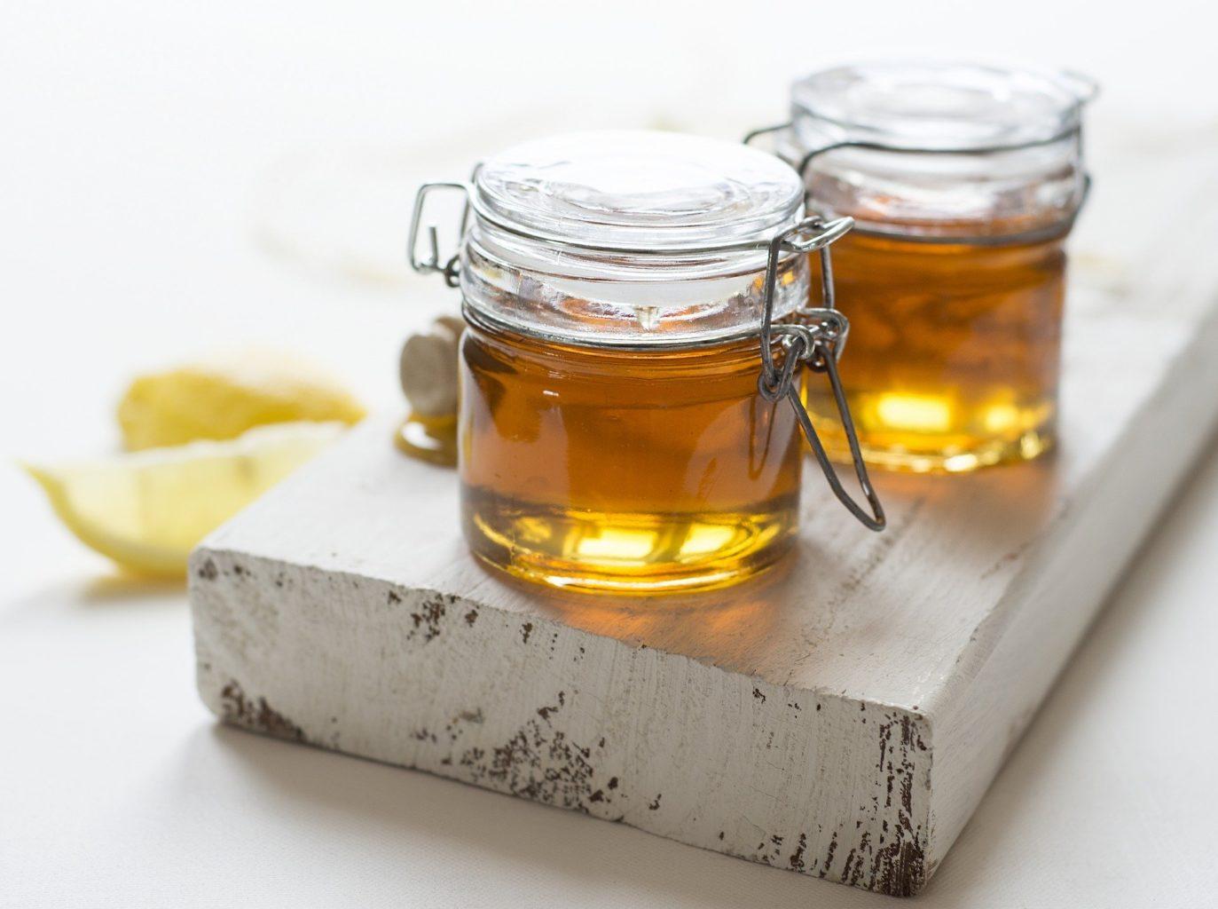 două borcane cu miere pe un suport alb, de lemn, cu felii de lămâie lângă