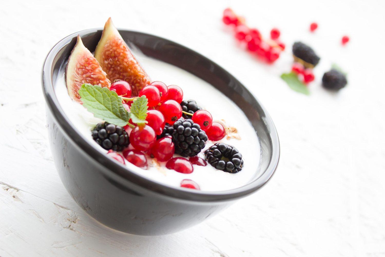 bol de iaurt grecesc, cu fructe de padure si smochine, in bol negru