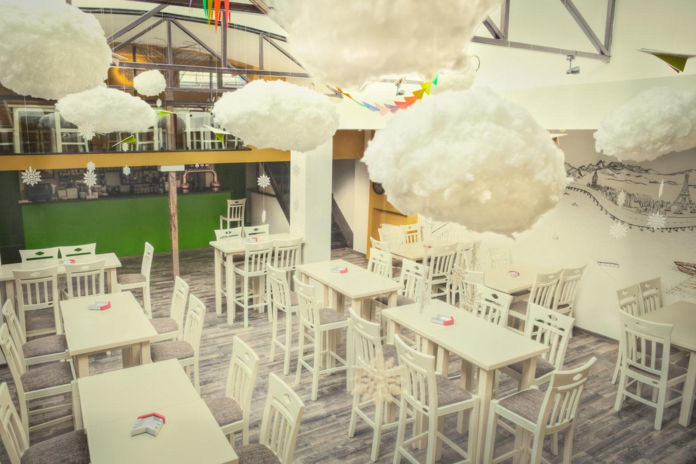 incapere de la journey pub cu mese si scaune albe si nori albi, decorativi, atarnati de tavan, una din cafenele moderne unde sa lucrezi relaxat