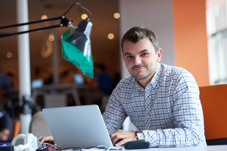 barbat tanar brunet, imbracat in camasa si cu laptopul in fata, cu o lampa de birou in dreptul lui, imagine reprezentativa pentru un tanar antrepenor, manager de restaurant care reduce costurile directe