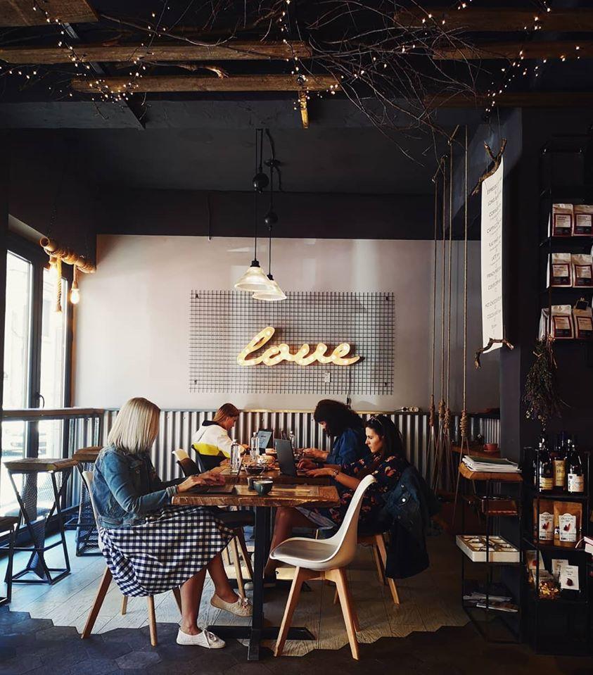 oameni lucrand la laptop, la masa in cafeneua UrBarn, cu ferestre mari si pereti cimentati si un semn luminos cu litere love