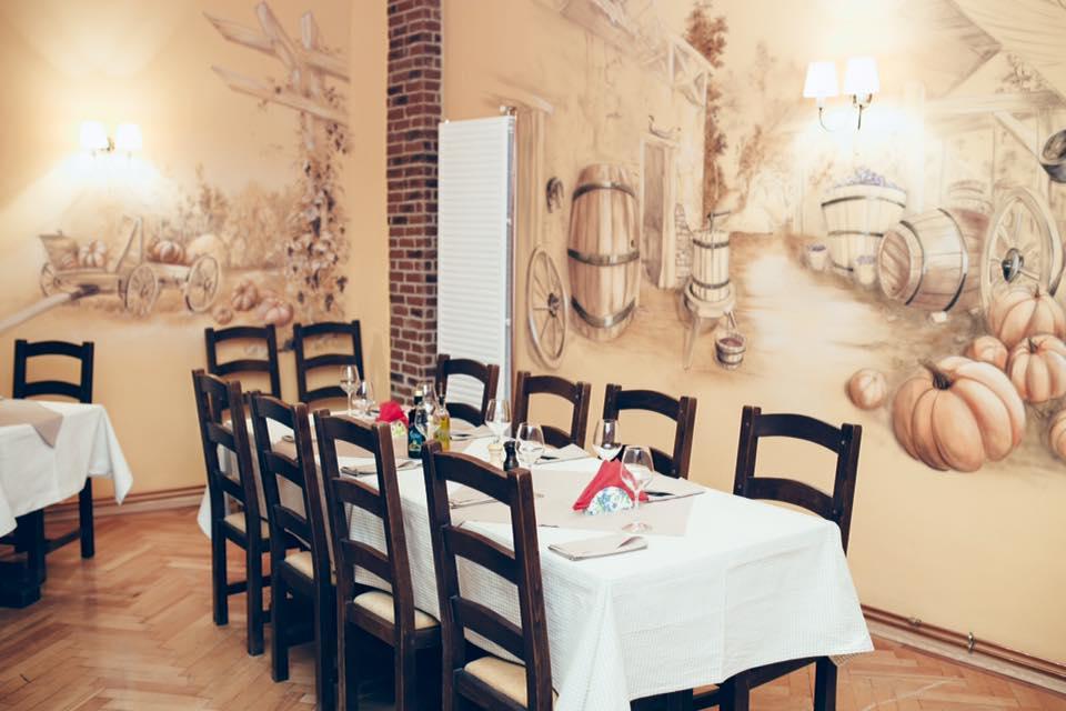 Imagine din restaurantul cu specific italian osteria Zucca, cu o masa lunga, cu fata de masa alba, scaune de lemn maro si pe fundal doi pereti crem, pictati