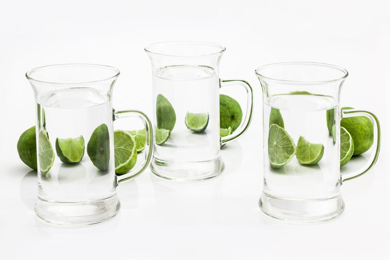 trei pahare de apa pe fundal alb, cu jumatati de lime langa, care taie pofta de mancare