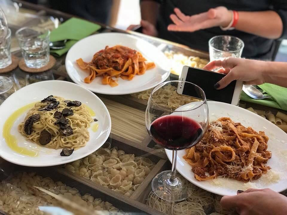 masa la restaurante fara gluten, cu trei farfurii de paste in prim plan, asezate pe masa, si un pahar de vin rosu