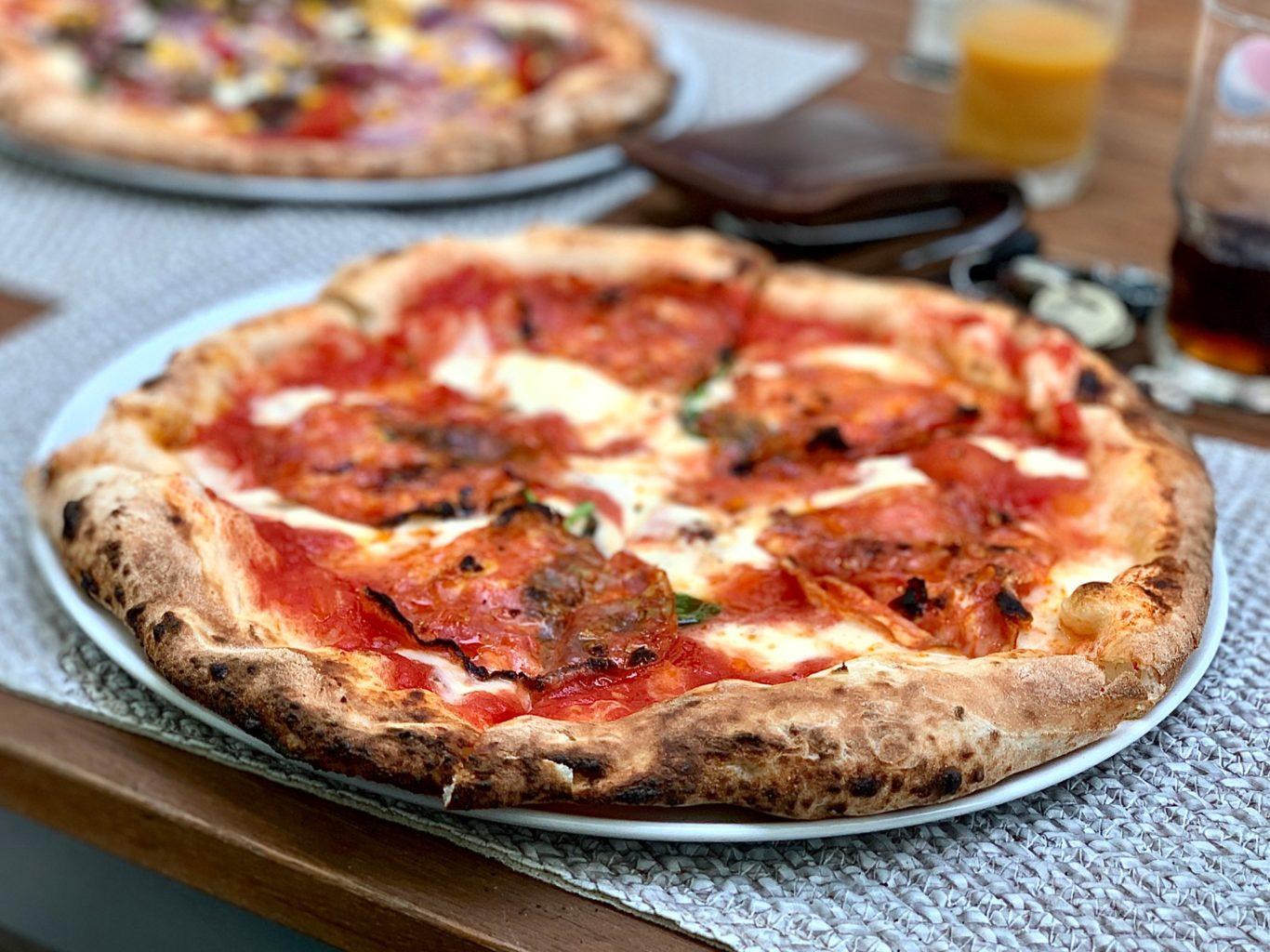 pizza ru blat rumen si crocant, mozzarella si sos de rosii, pe farfurie alba si stergar gri, pizza italiană București
