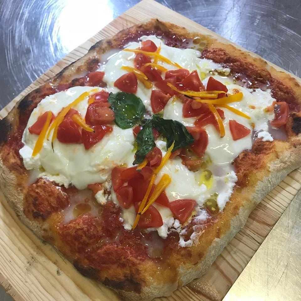 pizza patrata cu mozzarella, rosii taiate si busuioc, pe blat de lemn, de la gustosi Momenti, pizza italiană București