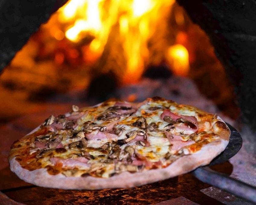 pizza cu multe ingrediente, pe paleta de fier, urmand a fi introdusa in cuptorul cu lemne in care arde focul
