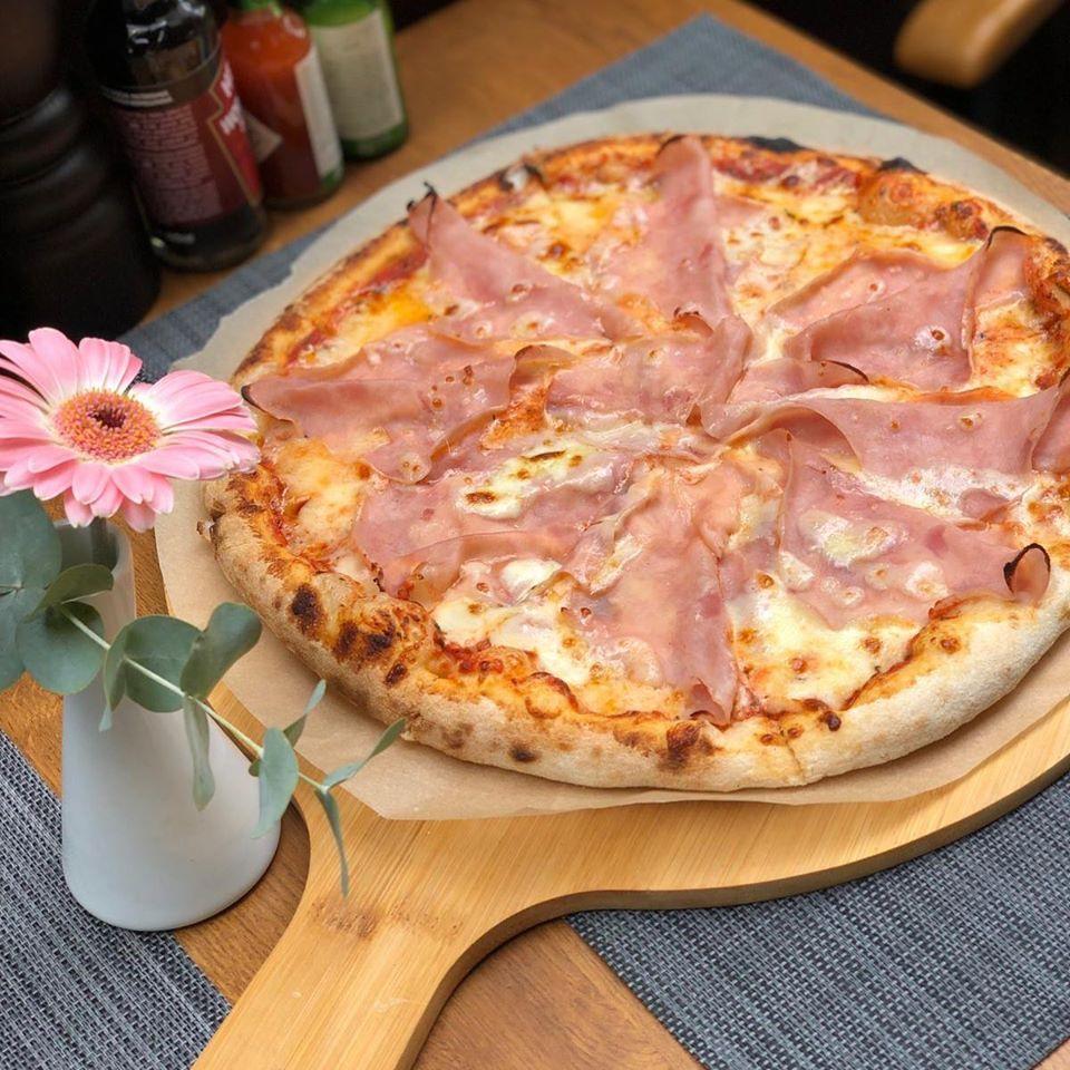 pizza pe cu prosciutto, servita pe platou de lemn rotund, asezat pe fundal gri si o vaza alba cu o floare roz asezata langa, pizza italiană în București
