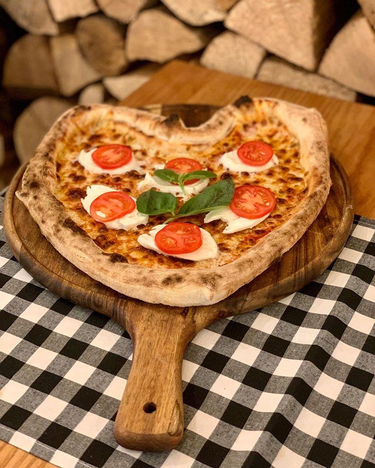 pizza in forma de inima, cu rosii, busuioc si mozzarella, pe platou de lemn pe fundal in ptratele alb negru