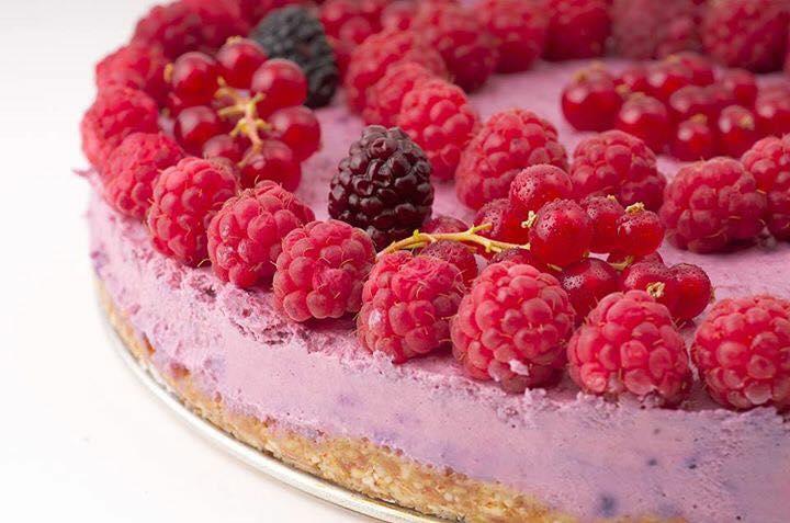 prim plan cu o bucata de tort raw, din fructe de padure, de culoare mov, ornat cu zmeura si mure, de la rawdia