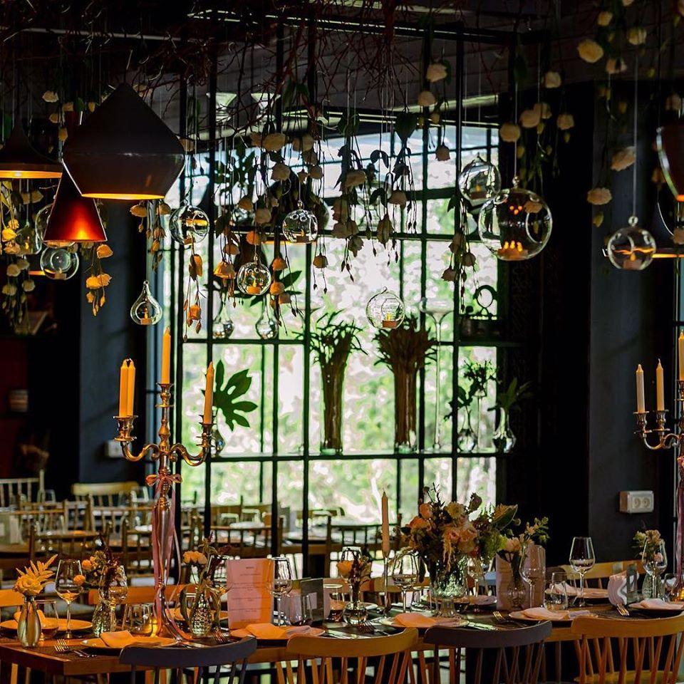 masă lungă de la restaurantul Il Locale, plina de ornamente florare, pahare, farfurii si candelabre. De tavan sunt atarnate aranjamente florale, corpuri de iluminat moderne si decoratiuni din sticla, iar in fundal se vede o fereastra mare si doi stalpi albastru inchis