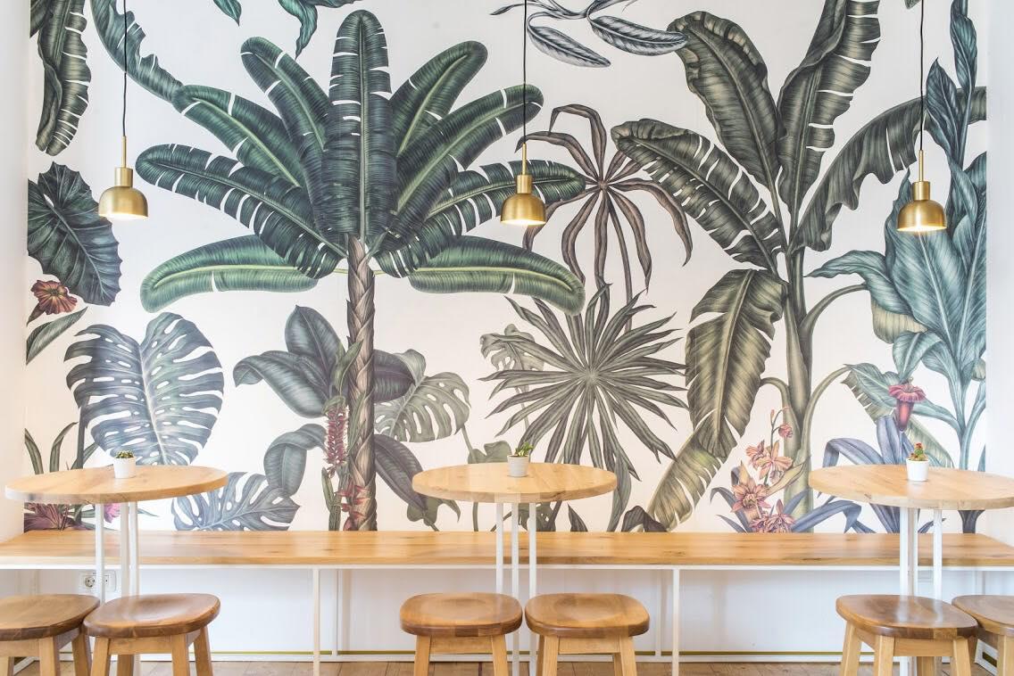 mese rotunde cu scaune rotunde, in fata unui perete mare cu palmieri, din restaurantul bite, una din cafenele moderne în care să lucrezi
